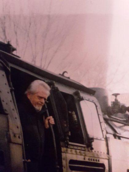 Ein Mann mit weißem Bart schaut aus einer Dampflock