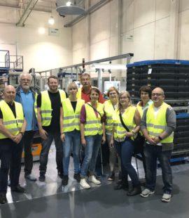 10 Mitglieder mit gelben Westen in einer Produktionshalle