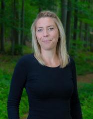Eine Frau, Anfang 30, mit blondem Haar und dunkelblauem Shirt steht vor Waldbäumen