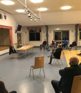 Viele Menschen sitzen in großem Abstand im Halbkreis vor einer Bühne, Florian Fahrtmann steht davor und referiert gerade