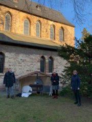 3 Personen stehen vor einer Kirche