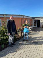 Florian Fahrtmann steht vor einem Altenwohnheim und eine Frau daneben mit zwei Blumensträußen