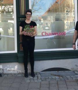 zwei Frauen und ein Mann stehen vor einem Schaufenster, eine hat ein Geschenk in den Händen