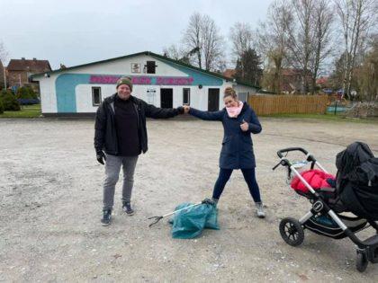 2 Personen stehen in großem Abstand vor einem mit Müll befüllten blauen Plastiksack