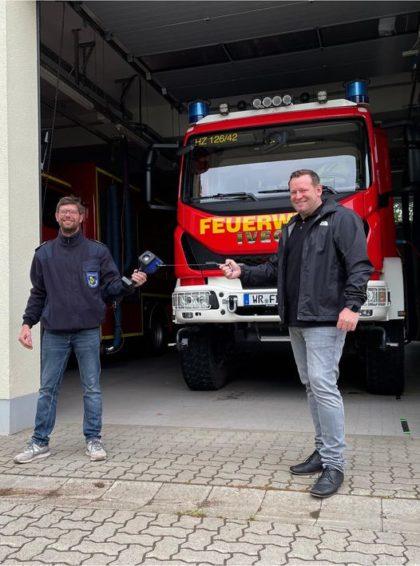 Florian Fahrtmann und Milan Fulst stehen vor einem Feuerwehrauto in der Garage