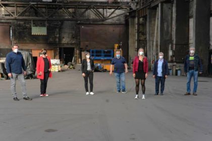 7 Personen stehen in weitem Abstand mit Mundschutz in einer alten Produktionshalle