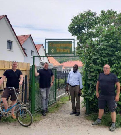 Dr. Karamba Diaby steht mit Florian Fahrtmann und anderen Personen in einer Gartenspartenanlage