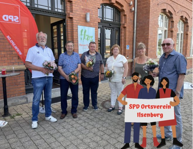 mehrere Personen stehen vor dem Bahnhof Ilsenburg mit einem Strauß Blumen in den Händen